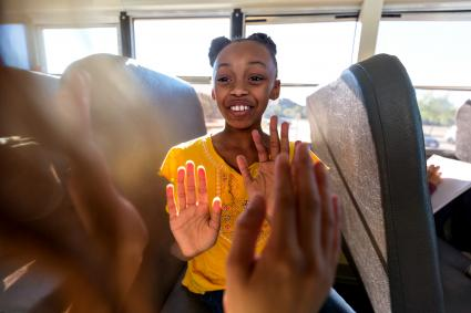 Girls clap and chant on a school bus ride