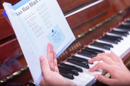 Man playing piano from a book Baa Baa Black Sheep