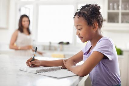 Girl writing food diary in kitchen