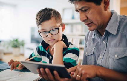 Father showing digital tablet to son