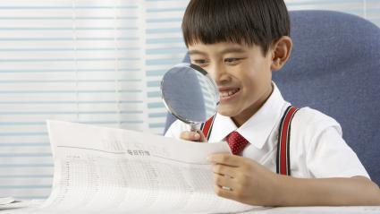 A boy reading newspaper with a magnifying glass