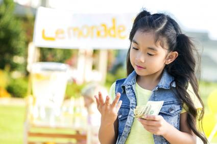 Young girl counts money made from lemonade stand
