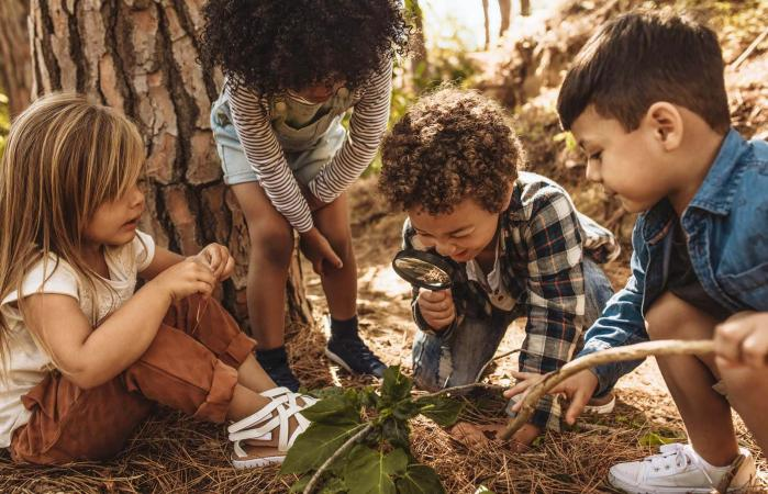 Kids in forest with a magnifying glass
