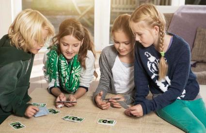 Four children playing card game