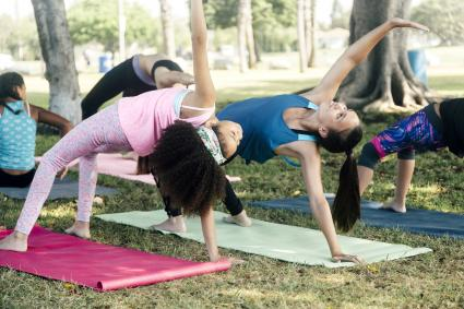 Schoolgirls practicing yoga pose on school playing field