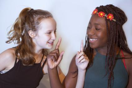 Two teenage girls playing charades