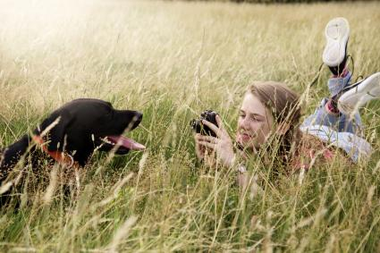 Teenager takes photos of her Labrador retriever dog in park