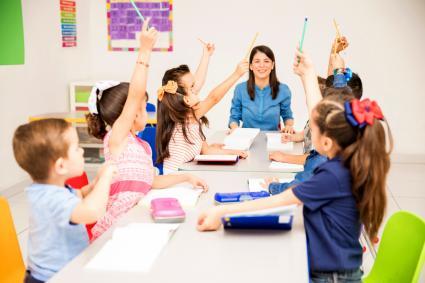 Kids raising their hands at school