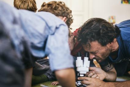 Father and sons using microscope during science lesson