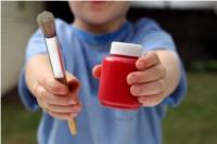 little boy holding red paint and paint brush