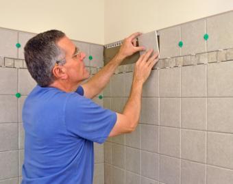 Man installing wall tile