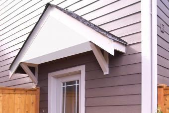 Wood awning overhanging front door.