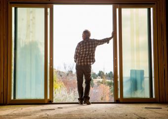 Senior man leaning in doorway