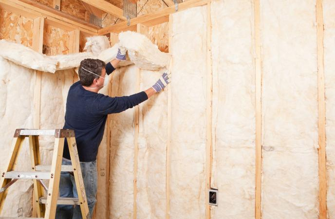 Man insulating wall with fiberglass batt