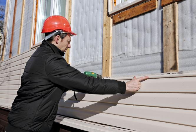 Man installing vinyl siding on house