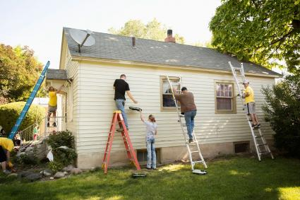 People painting and working on house