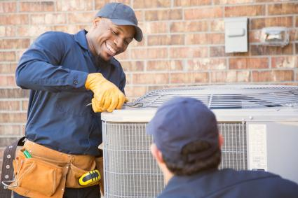 Repairmen working on air conditioning unit