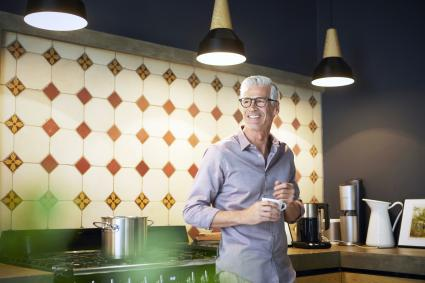 Smiling mature man at home in kitchen