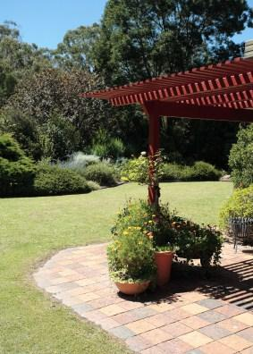 An arbor provides shade to a patio.