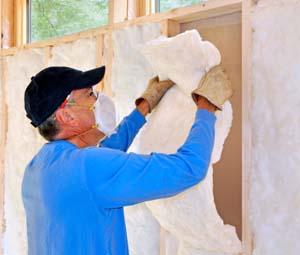 Man installing insulation in wall.