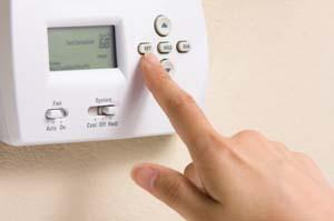 Hand programming a low-voltage thermostat.