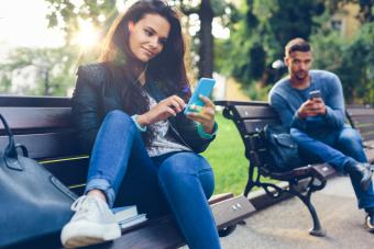Young couple in the park texting
