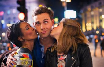 Flirty man kissed by two women