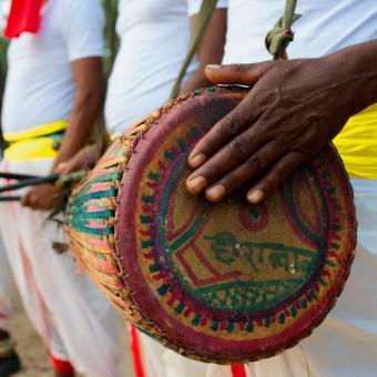 Tribal drummer banging on drum
