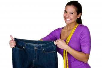 Woman holding up oversize jeans