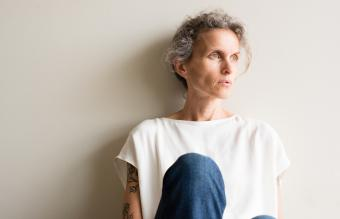 Woman sitting with back to wall