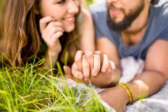 Affectionate couple holding hands while lying on the grass