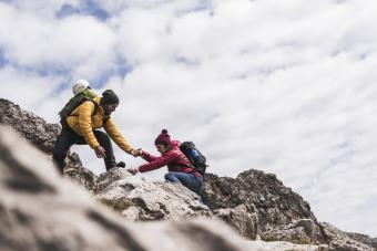 Man helping woman while hiking
