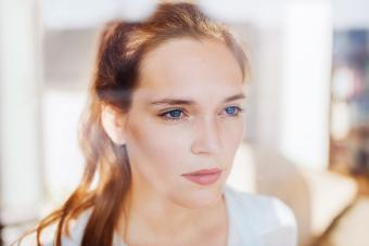 Woman looking serious behind a window