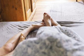 Young couple's feet while lying in bed