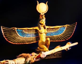 Egyptian goddess Isis kneeling with traditional magic wand made with quartz