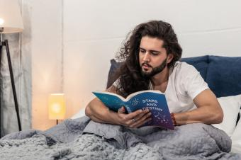 Man reading horoscope in bed