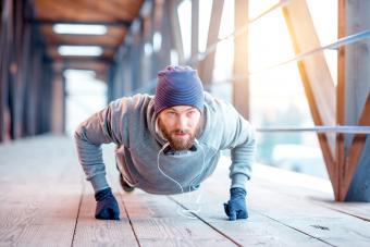 Man in hat and sweatshirt doing pushing-ups outdoors
