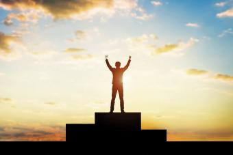 Silhouette Man With Arms Raised Standing Winners Podium Against Sky