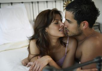 couple about to kiss on a bed