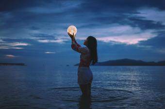 optical illusion of woman holding moon
