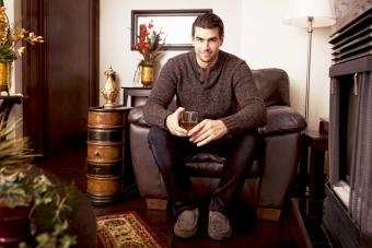 Man sitting with a drink in a brown room