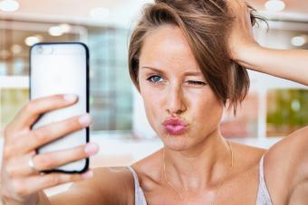 Vain woman looking at herself in mirror