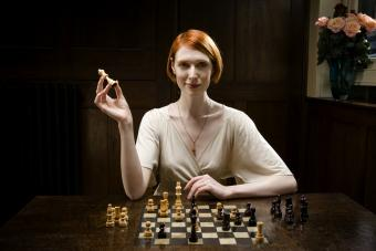 Woman holding up queen chess piece and smiling