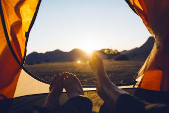 Couple watching the sun setting from tent