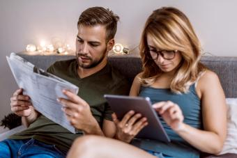 Couple Reading Newspaper And Listing Social Media