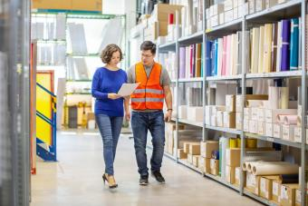 Manager discussing with foreman while walking by storage racks in large warehouse