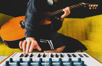 male playing guitar and keyboard