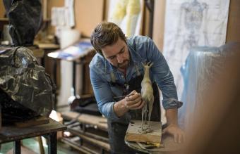 Sculptor working in studio