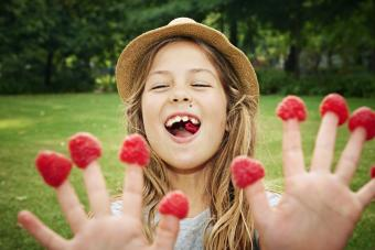 Girl with raspberries on fingers