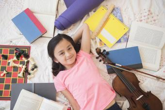 Girl laying on floor with hobbies and homework
